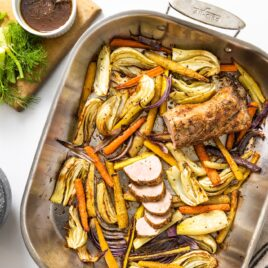 Top down view of white countertop with steel pan with sliced vegetables and roasted pork with slices cut off end