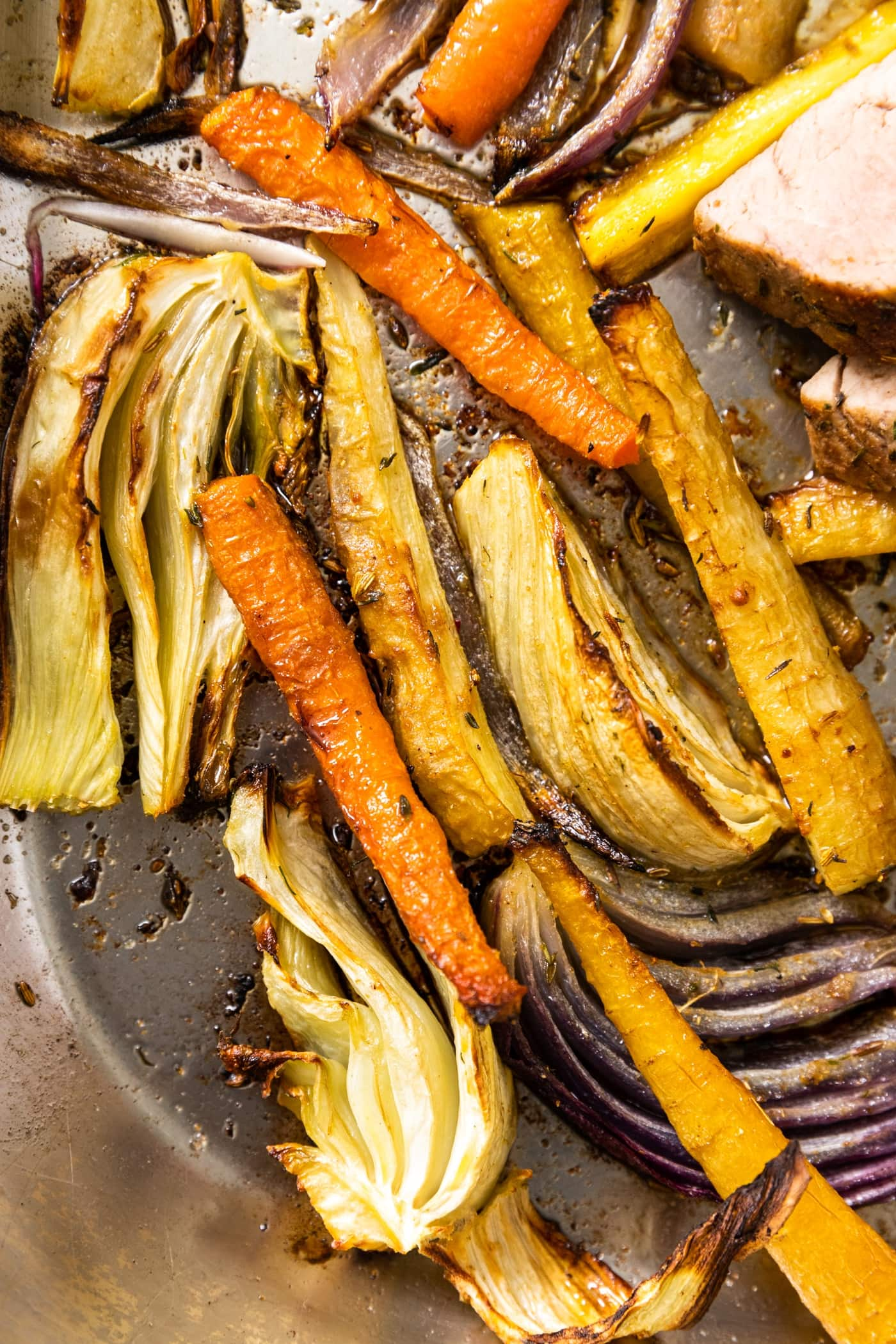 Top down view of roasted carrots and slices of fennel bulb sitting in roasting pan