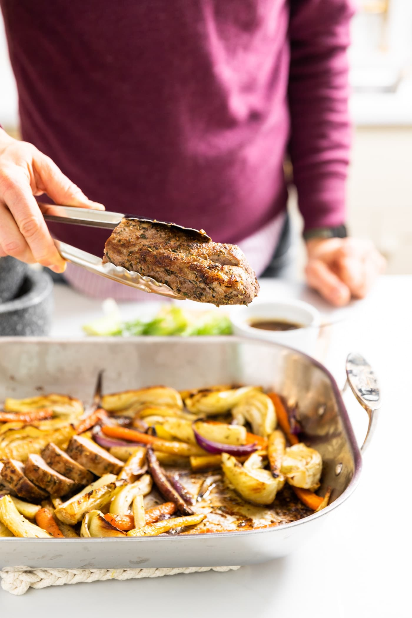 Hand holding tongs clutching a pork tenderloin roast with pan below it filled with slices of roasted vegetables all on white countertop