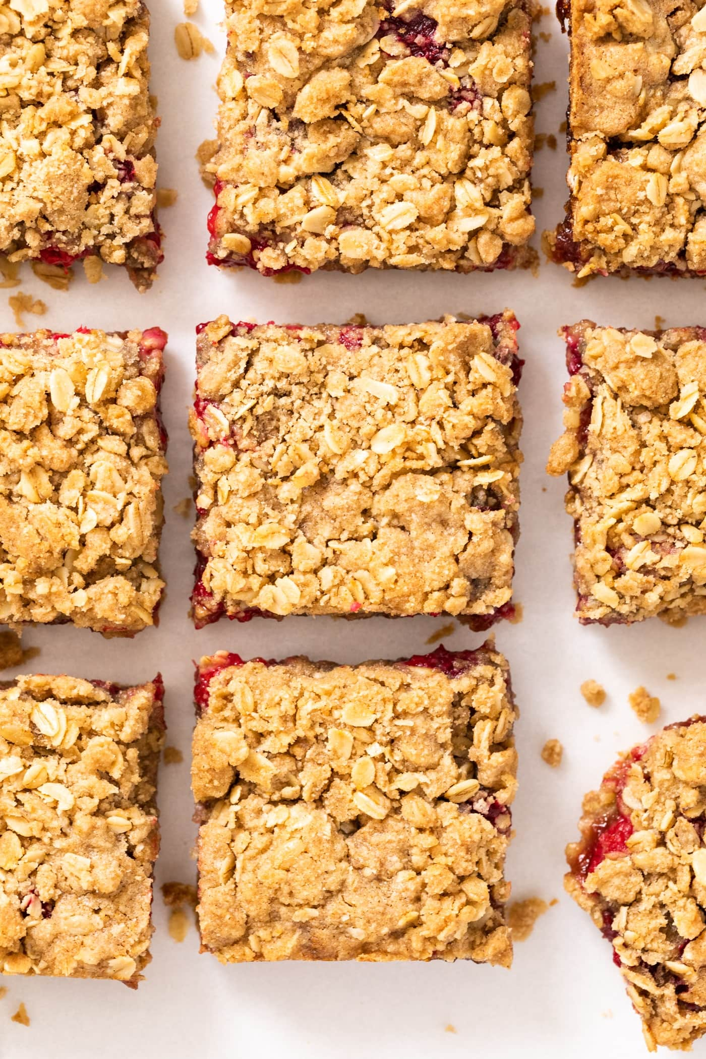 Top down view of square pieces of golden colored crumb bars with a red raspberry filling peeking out