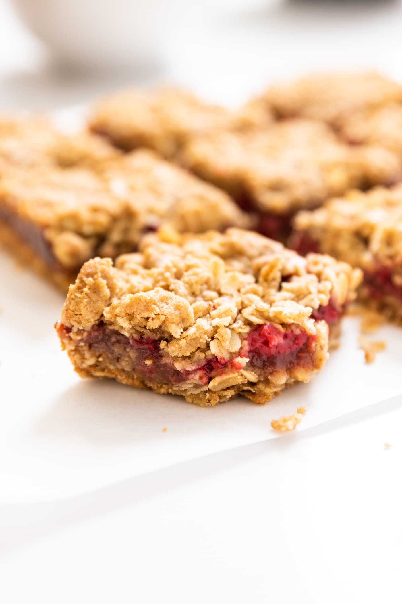 One square raspberry crumb bar sitting on white piece of parchment with a bit of red colored filling oozing out with extra bars in background
