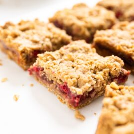 Crumb bars cut into slices filled with raspberry filled all on a white countertop