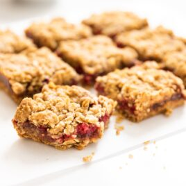 Nine square pieces of raspberry crumb bars sitting one white piece of parchment on white countertop