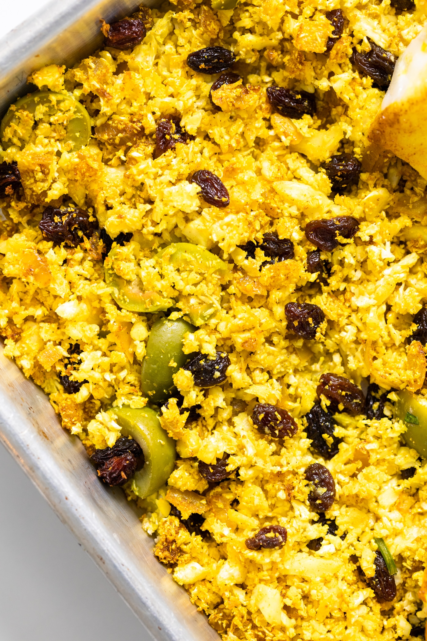 Top down view of yellow colored cauliflower rice with pieces of olives and raisins mixed amongst all on sheet pan