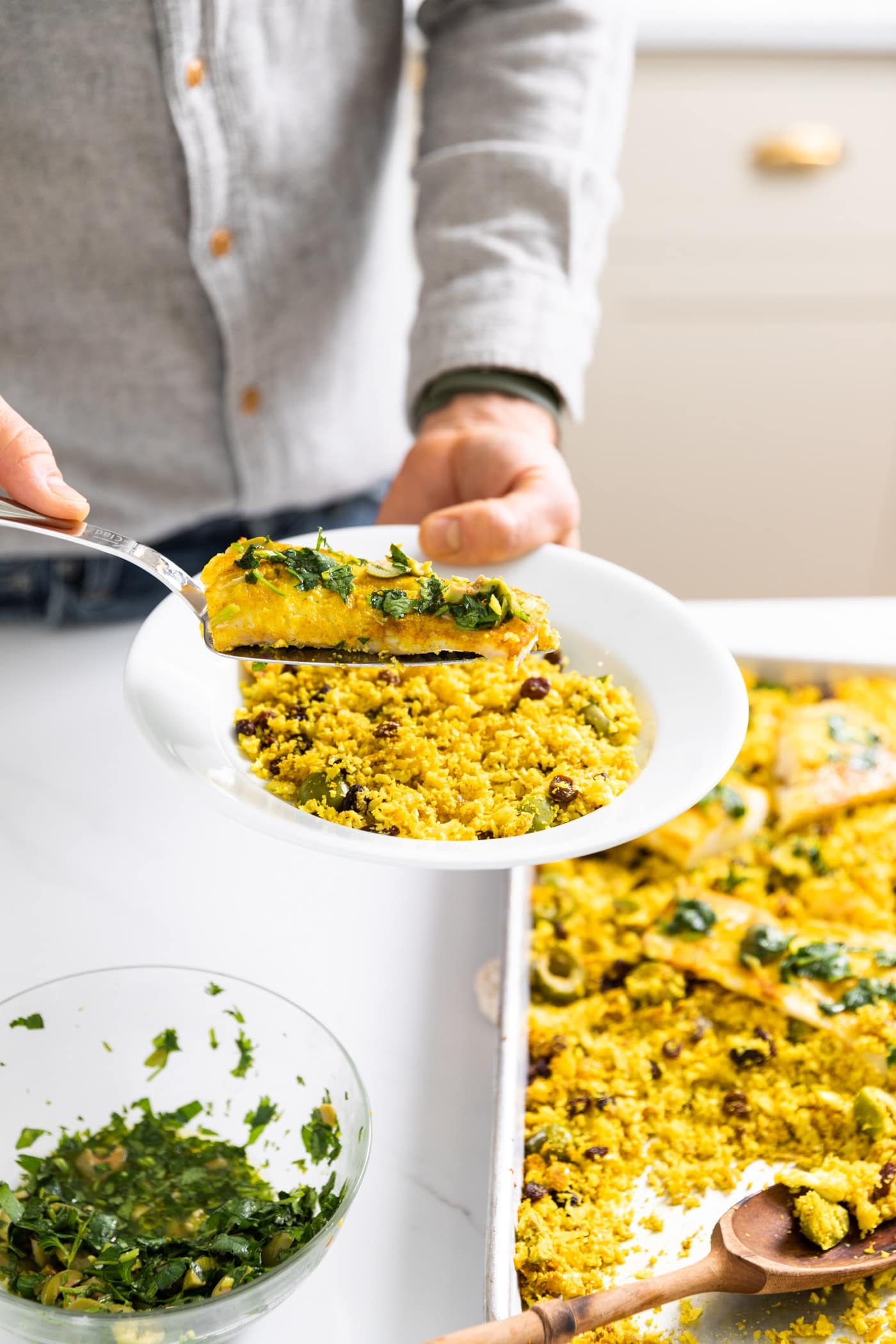 White plate held by man wearing a gray button down shirt putting piece of fish onto bed of yellow colored cauliflower rice