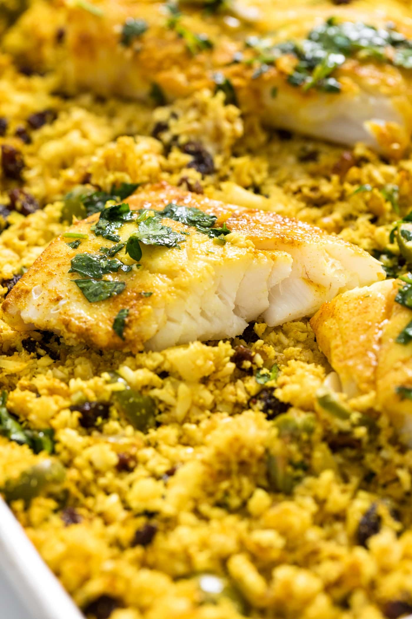 Piece of fish split in half sitting on bed of yellow cauliflower rice with green mix on top
