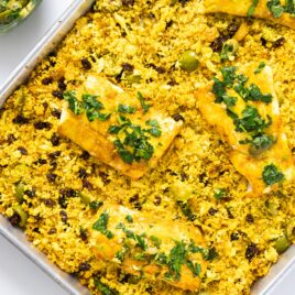 Top down view of sheet pan with yellow colored cauliflower rice with cod filets placed on top all on white surface