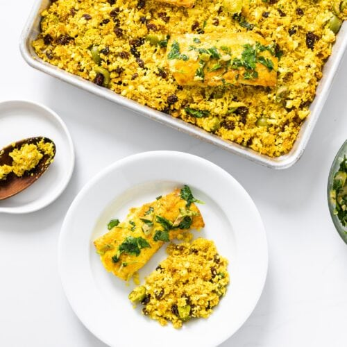 Top down view of white countertop with white plate and sheet pan containing yellow colored fish and cauliflower rice