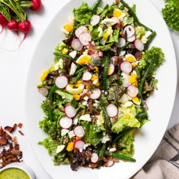 Top down view of white platter filled with green lettuce topped with spring vegetables with extra dressing on the side all on white countertops