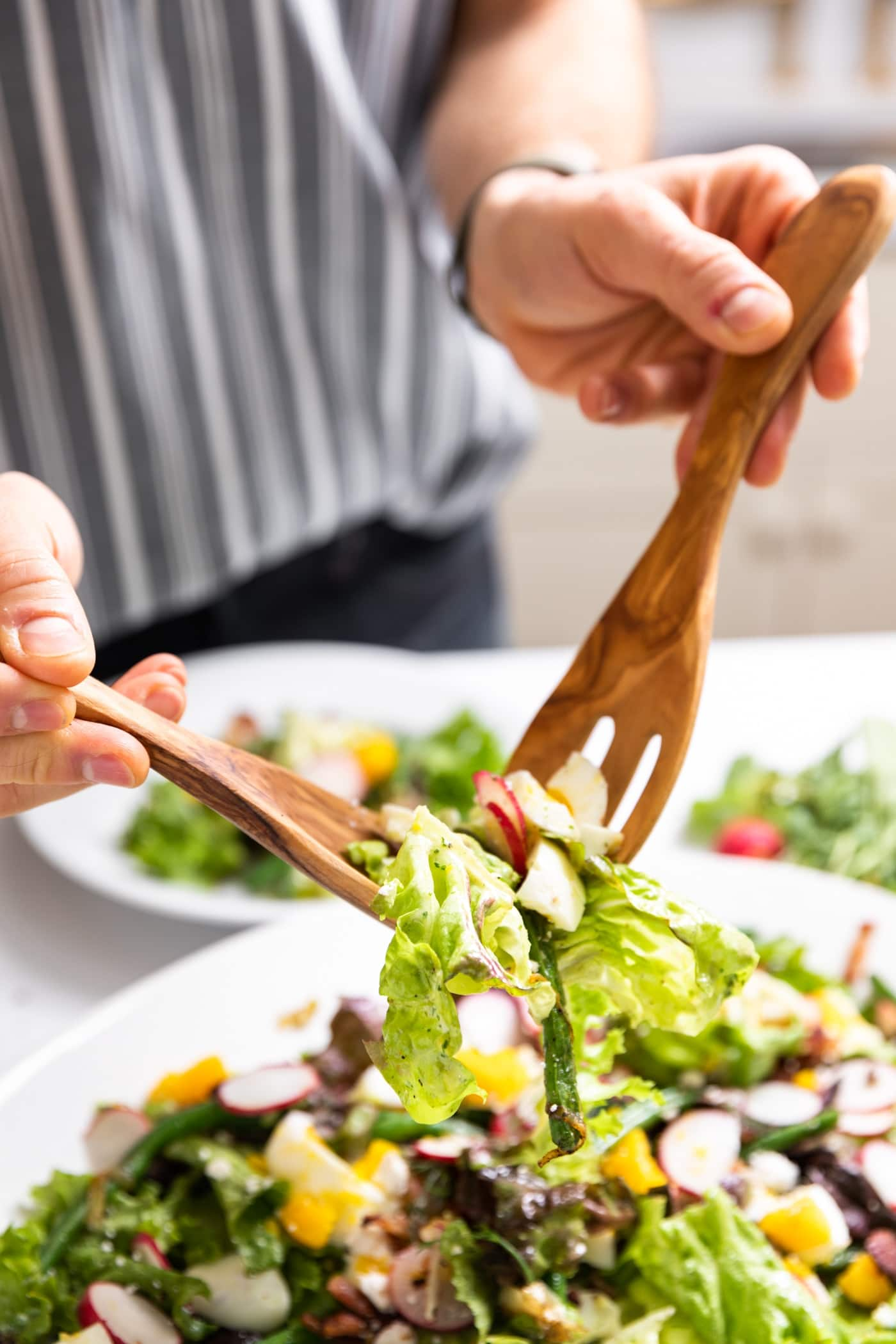 Two hands holding wooden salad tongs lifting up pieces of green lettuce with platter filled with rest of salad below