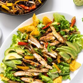 Top down view of white platter filled with salad greens and topped with grilled chicken pieces and grilled fajita vegetables all on white countertop
