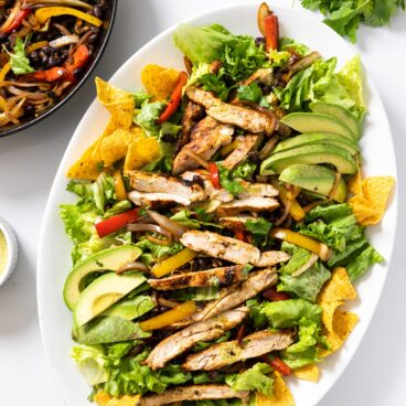 Top down view of white platter filled with salad greens and topped with grilled chicken and tortilla chips with extra grilled vegetables on the side in black skillet