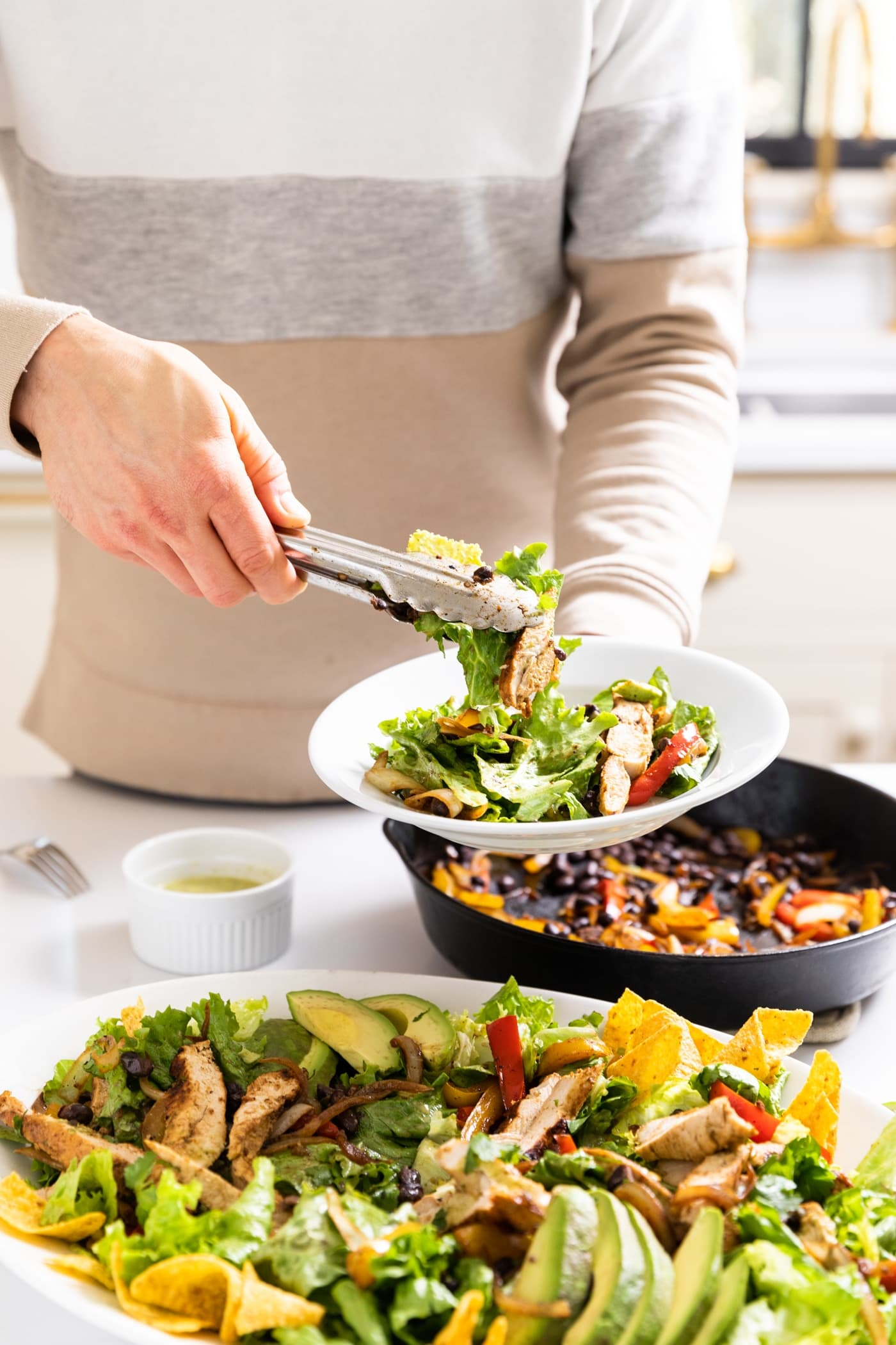 Hand holding tongs putting salad on white serving plate with rest of salad in platter below with black skillet filled with peppers in background