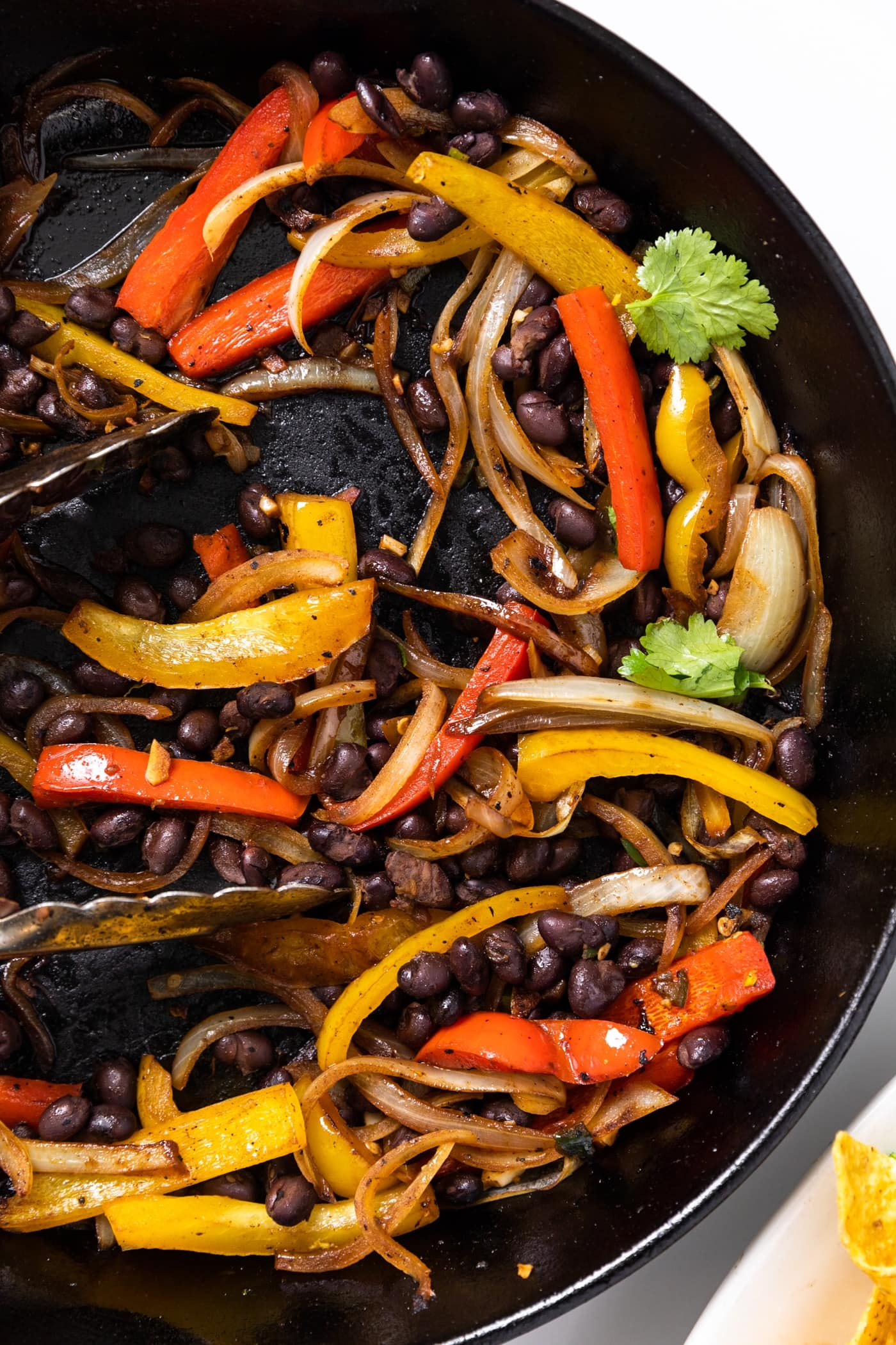 Top down view of black skillet filled with red and yellow peppers along with black beans all on white countertop