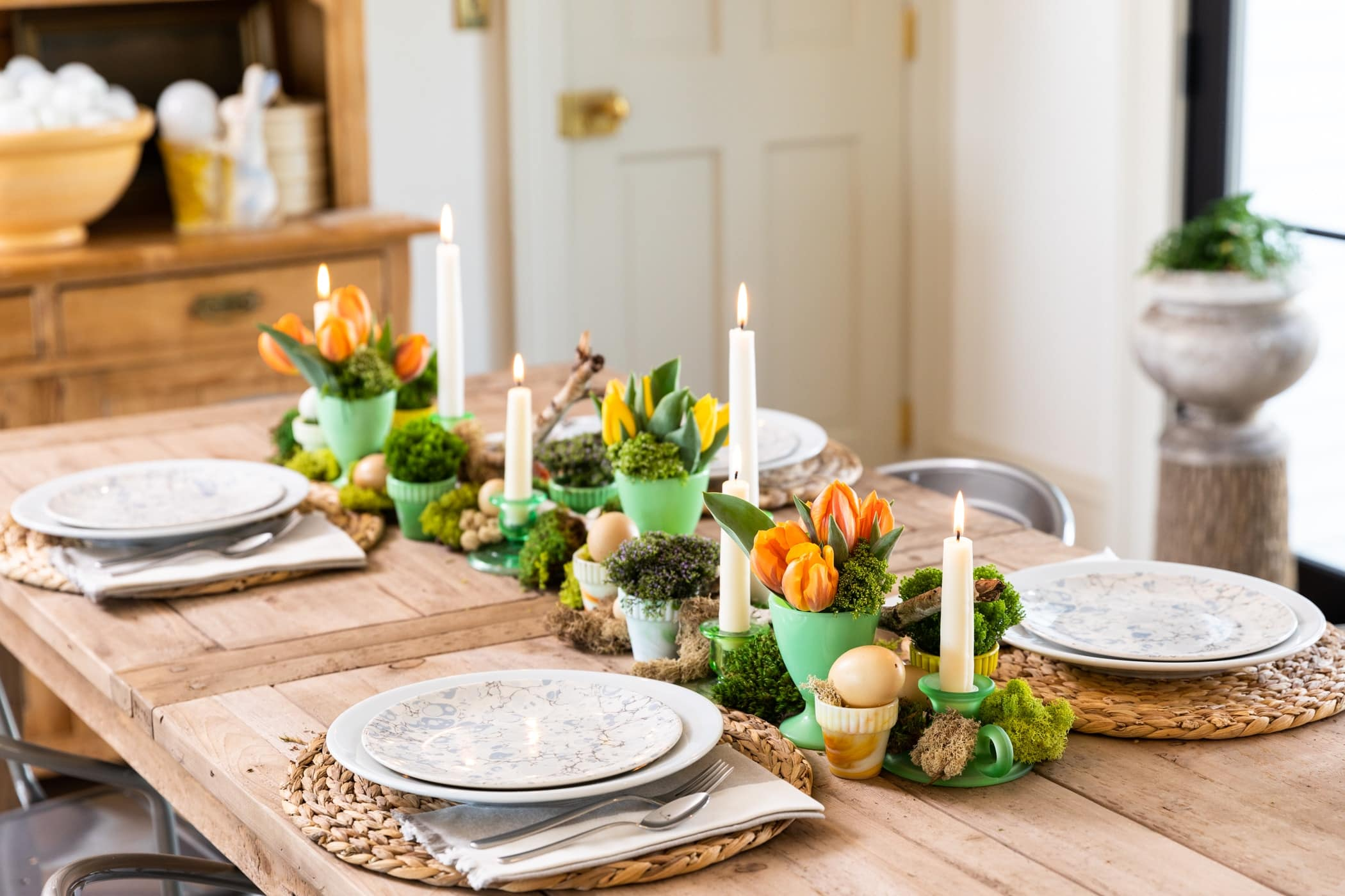 Wooden table spread spread with freshly colored tulip flowers in green vases with plates set around table