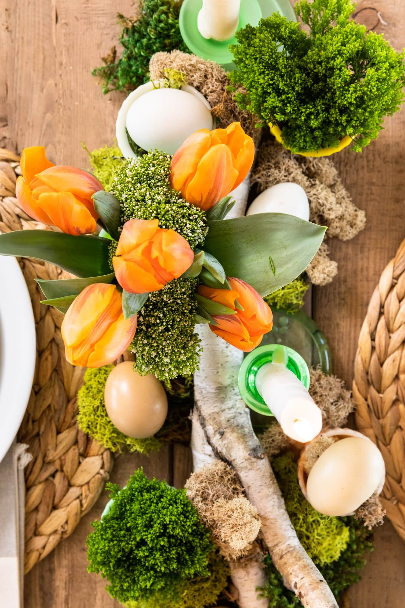 Top down view of tabletop with green moss, orange tulips, birch log, and set with plates