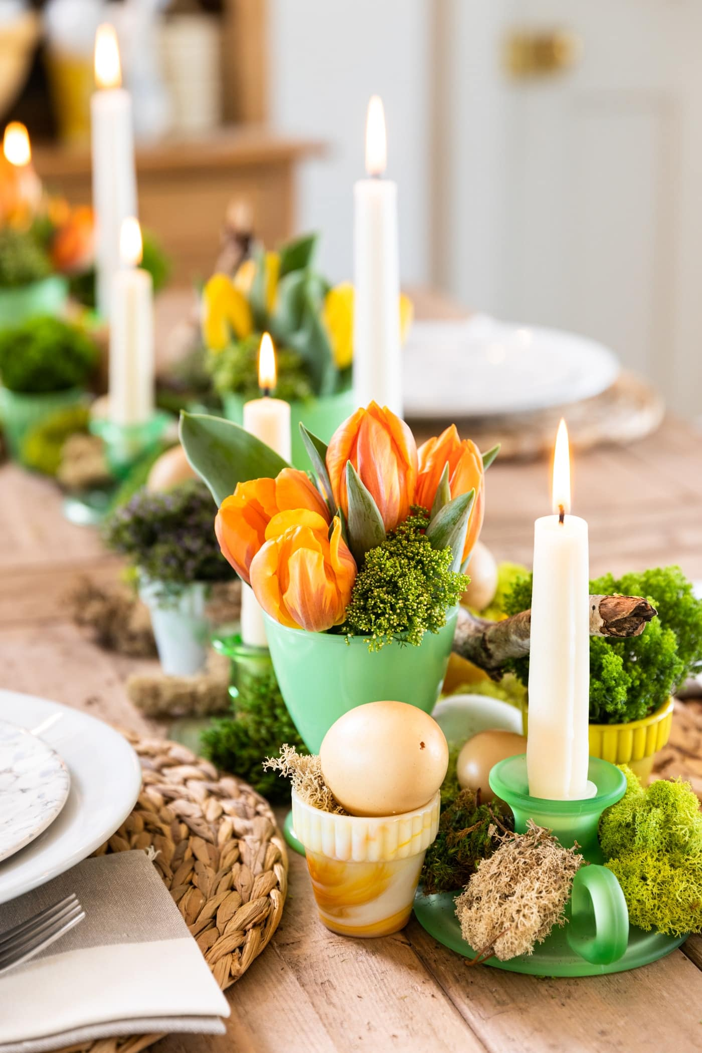 Green vase filled with orange tulips all on wood table with candles lit and white plates set around
