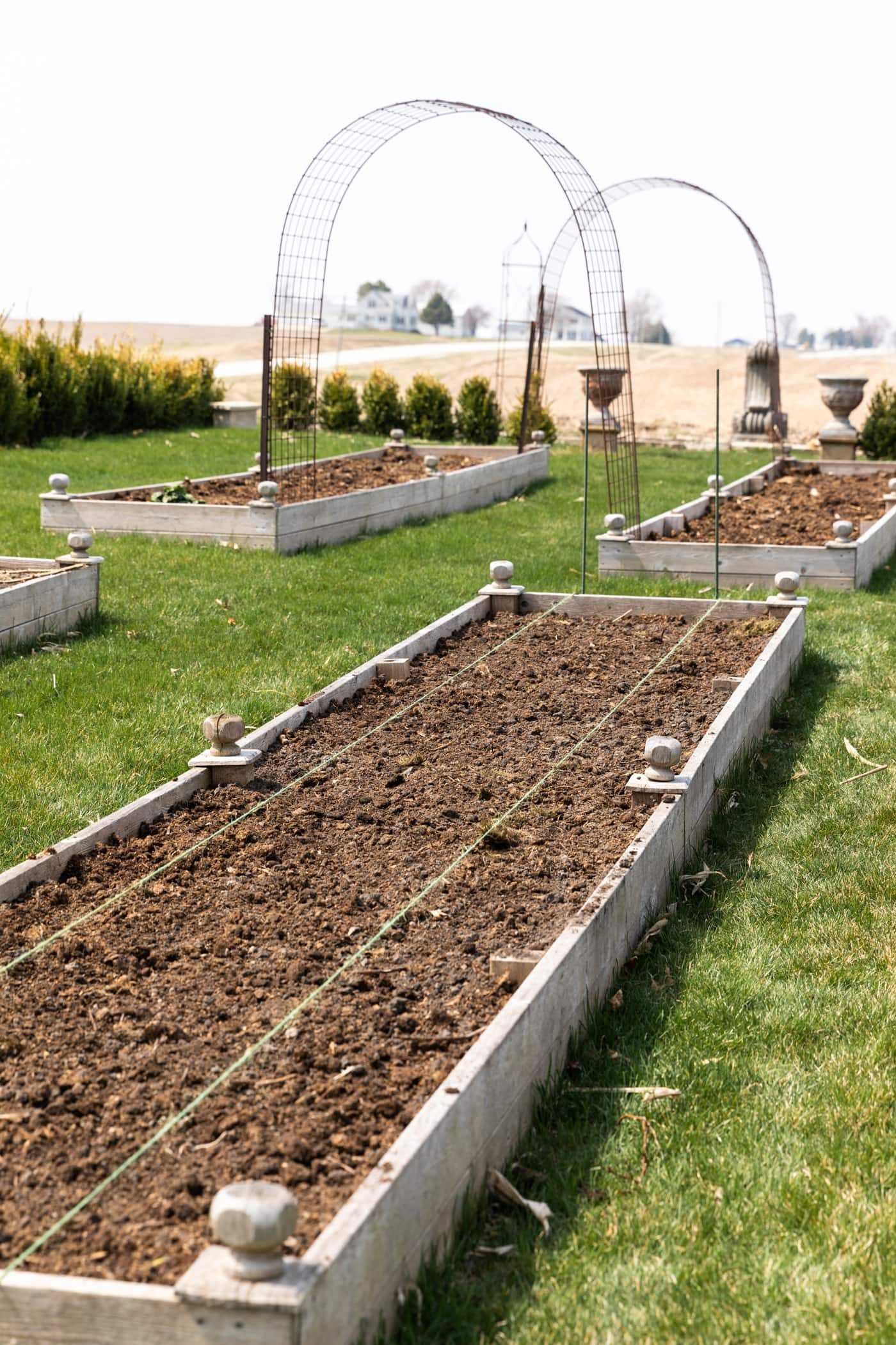 Raised garden bed filled with dirt surrounded by green grass with arches in distance