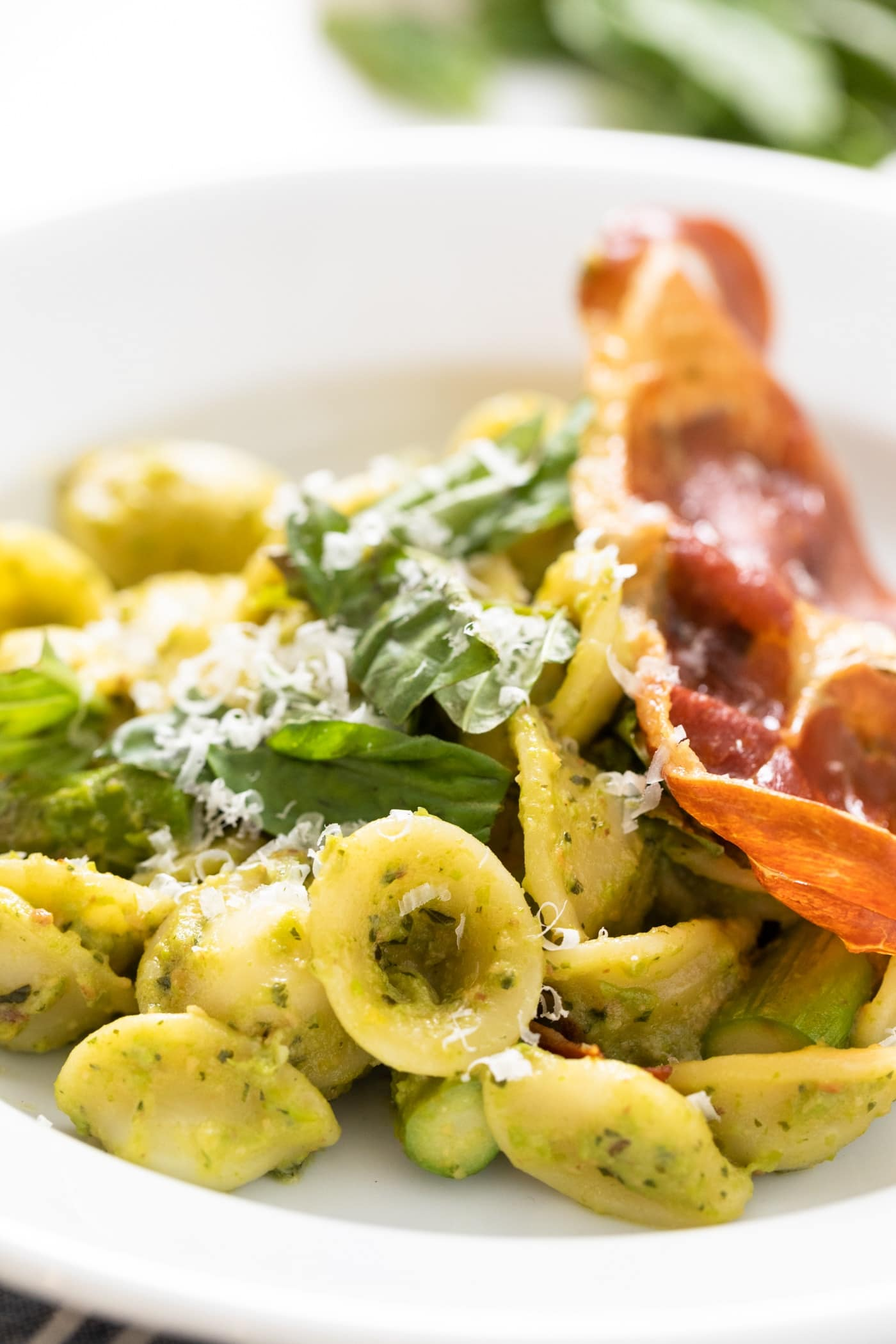 Close up view of pieces of pesto covered pasta sitting on white plate with slice of crispy prosciutto and basil leaves sitting on top