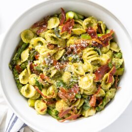 Top down view of yellow pasta covered in pesto sauce and topped with pieces of crispy prosciutto all on white countertop