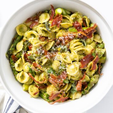 Top down view of large white bowl filled with pesto covered pasta mixed with crispy pieces of prosciutto and asparagus all on white countertop