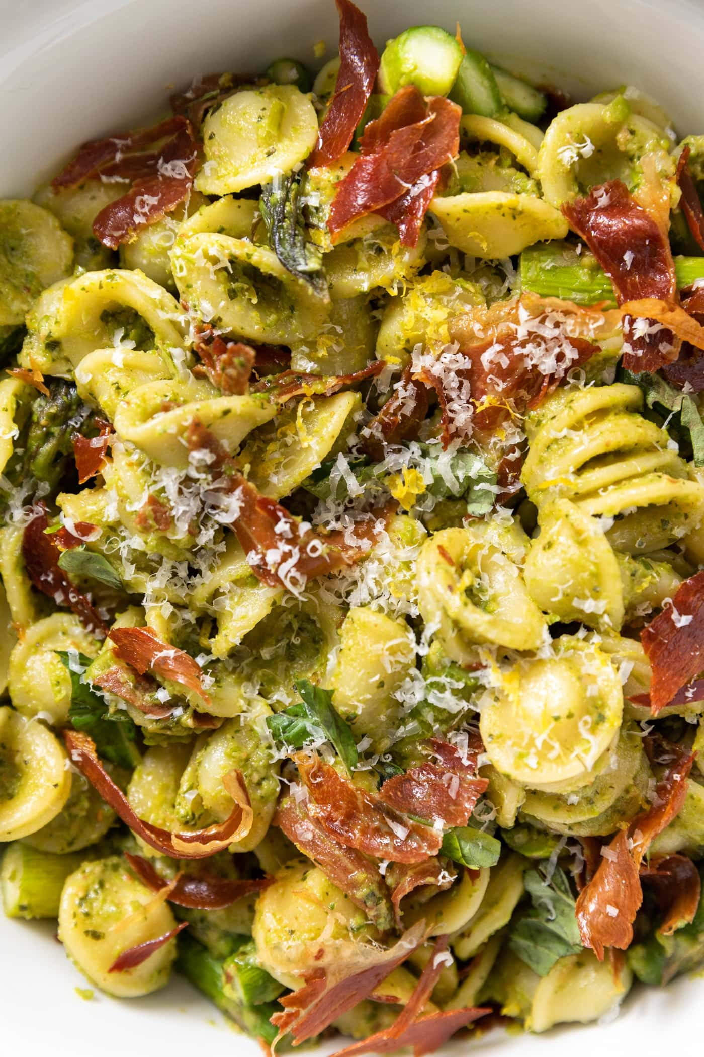 Close up view of pieces of yellow colored pasta mixed with asparagus and pieces of crispy prosciutto all in large white bowl