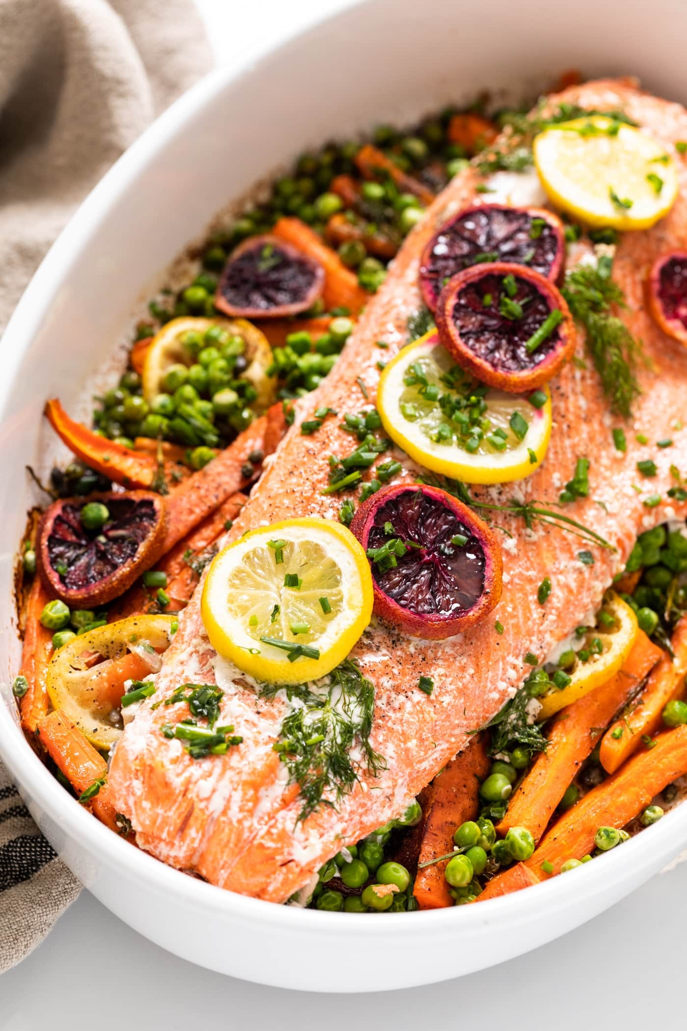 Large white platter filled with carrots and topped with filet of salmon and slices of lemon and orange pieces