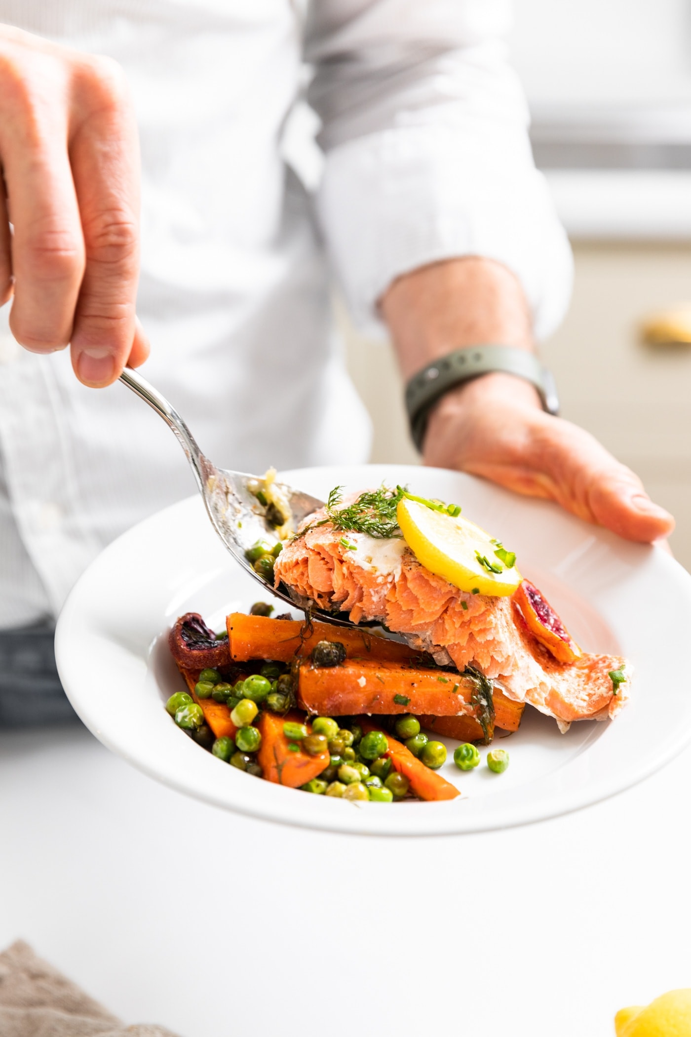 Hand holding white plate with peas and carrots with a filet of salmon being placed on plate