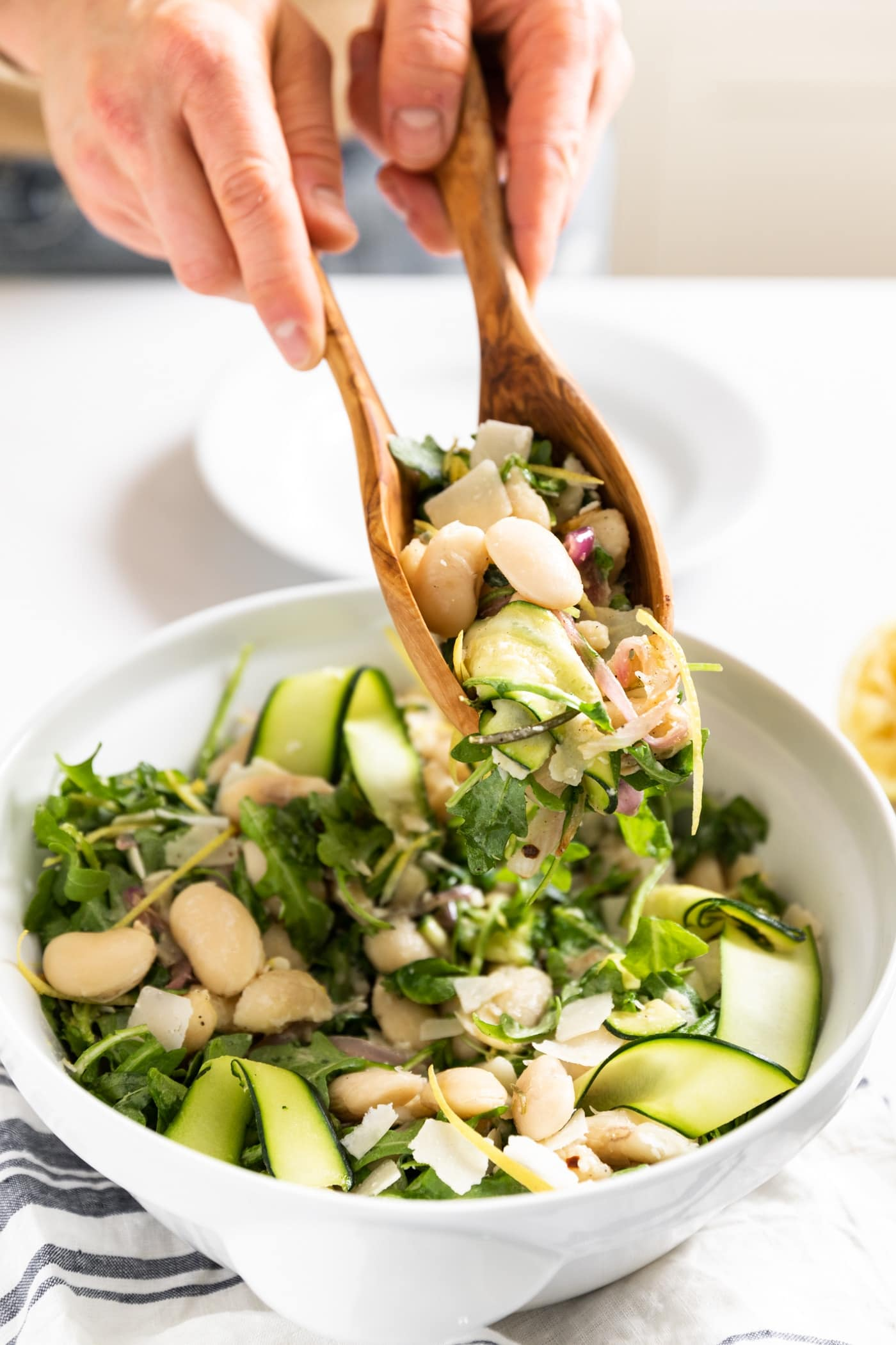 Close up view of large white bowl with two wood tongs holding a combination of white beans and greens