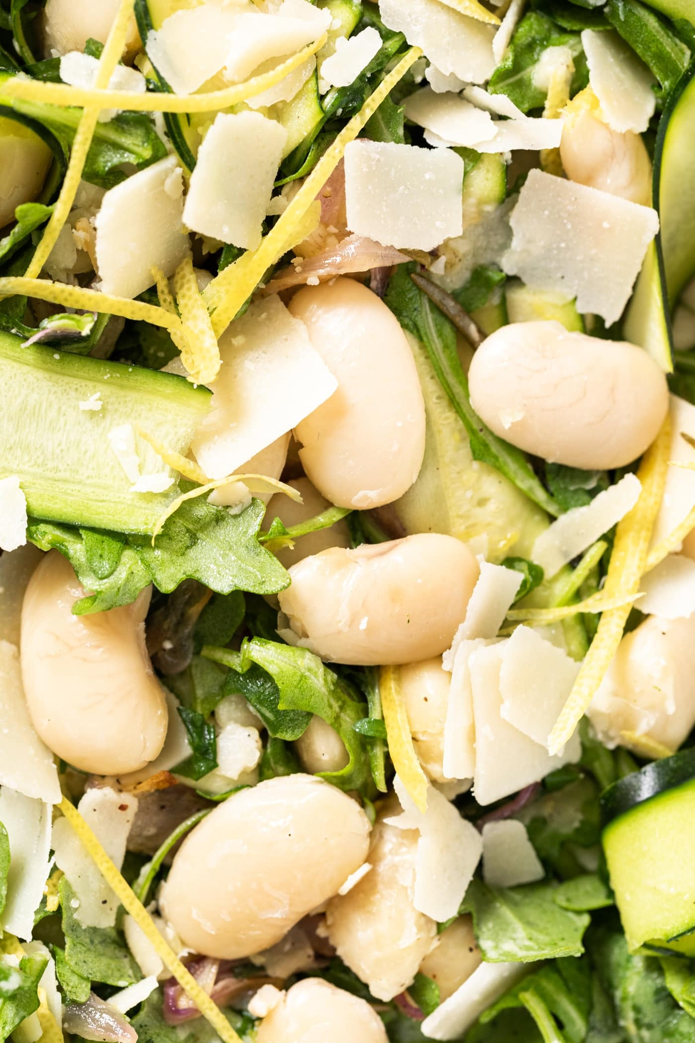 Close up view of large white beans nestled among greens and Parmesan and lemon zest