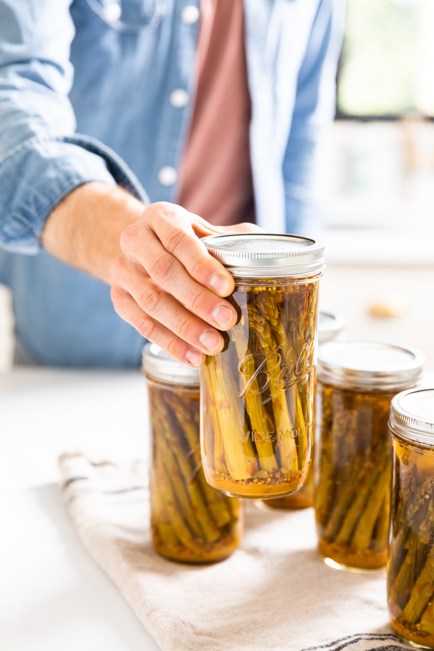 Hand holding glass jar with spears of pickled asparagus with other jars sitting around all on white countertop