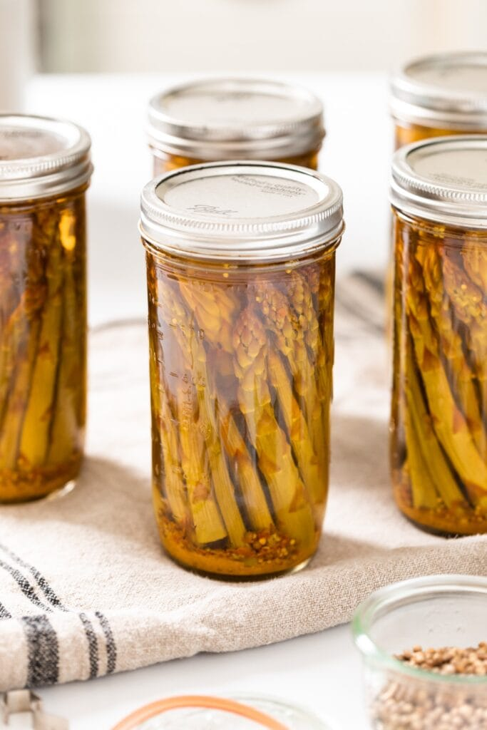 Glass canning jars filled with spears of asparagus all sitting on cloth with open jars of spices around