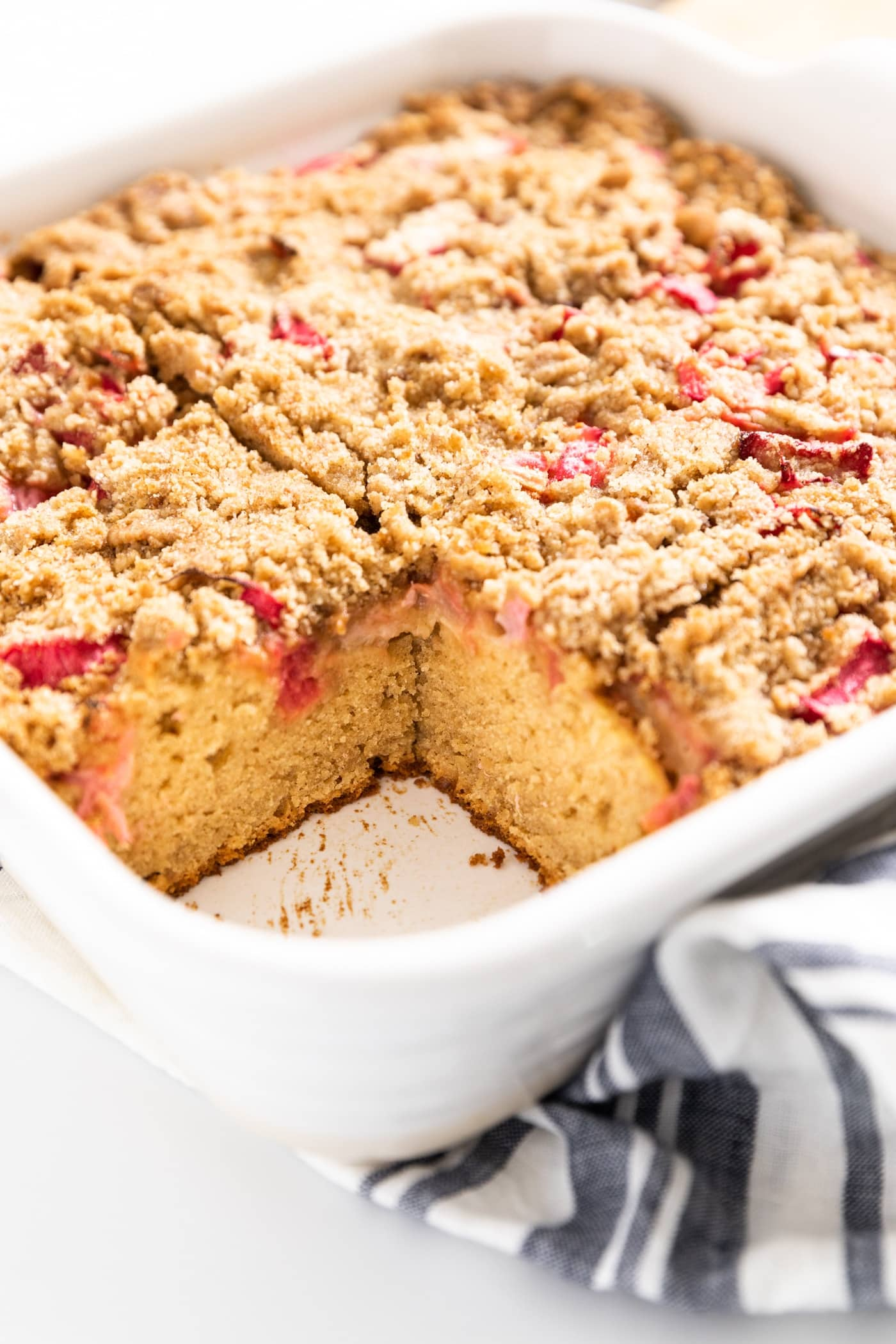Close up view of interior of coffee cake with pieces of rhubarb within all on white surface