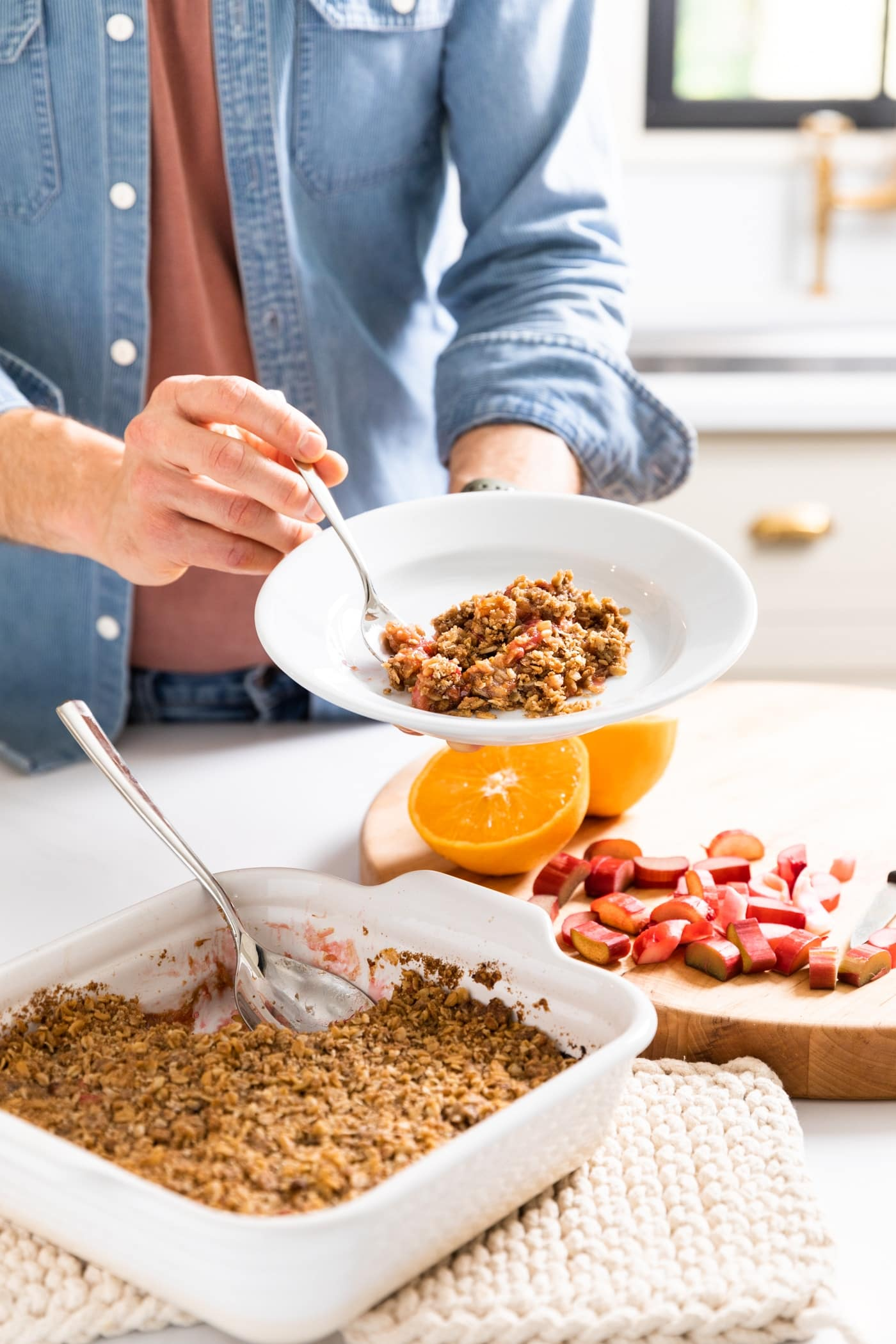 Man with blue shirt holding white plate with scoop of rhubarb crisp taken out of pan below with extra cut rhubarb in background