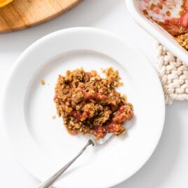 Top down view of white plate filled with brown and red colored rhubarb crisp with baking container sitting beside all on white countertop
