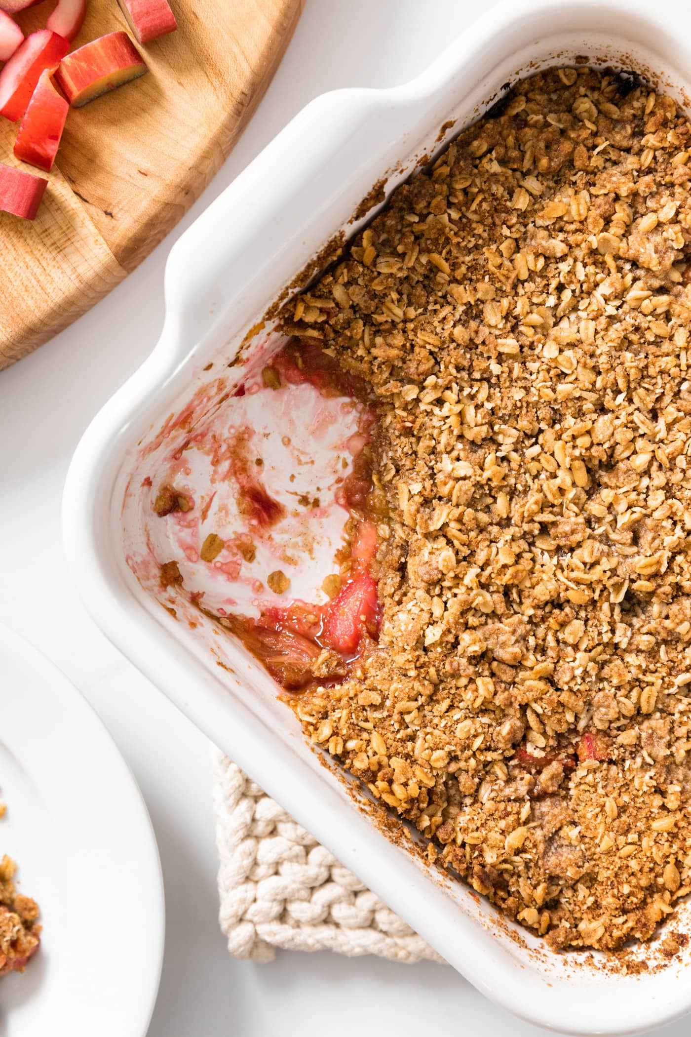 Top down view of white baking dish filled with rhubarb crisp with light brown topping with a scoop taken out