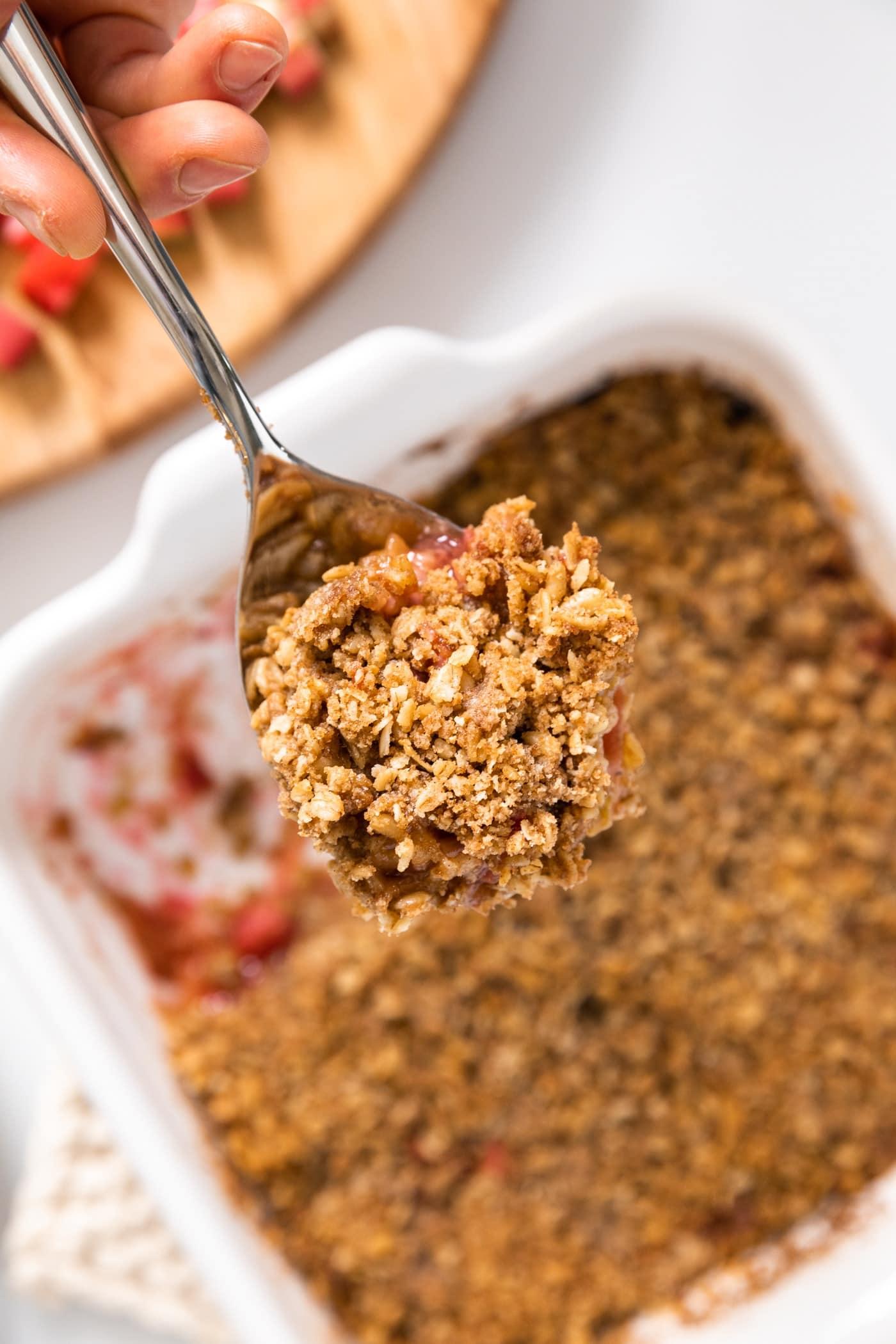 Large spoon holding scoop of rhubarb crisp from pan below
