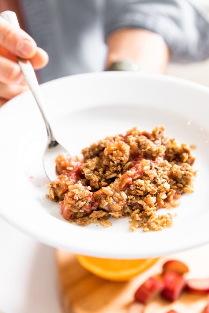 Close up view of red and brown colored rhubarb crisp sitting on white plate with hand holding fork