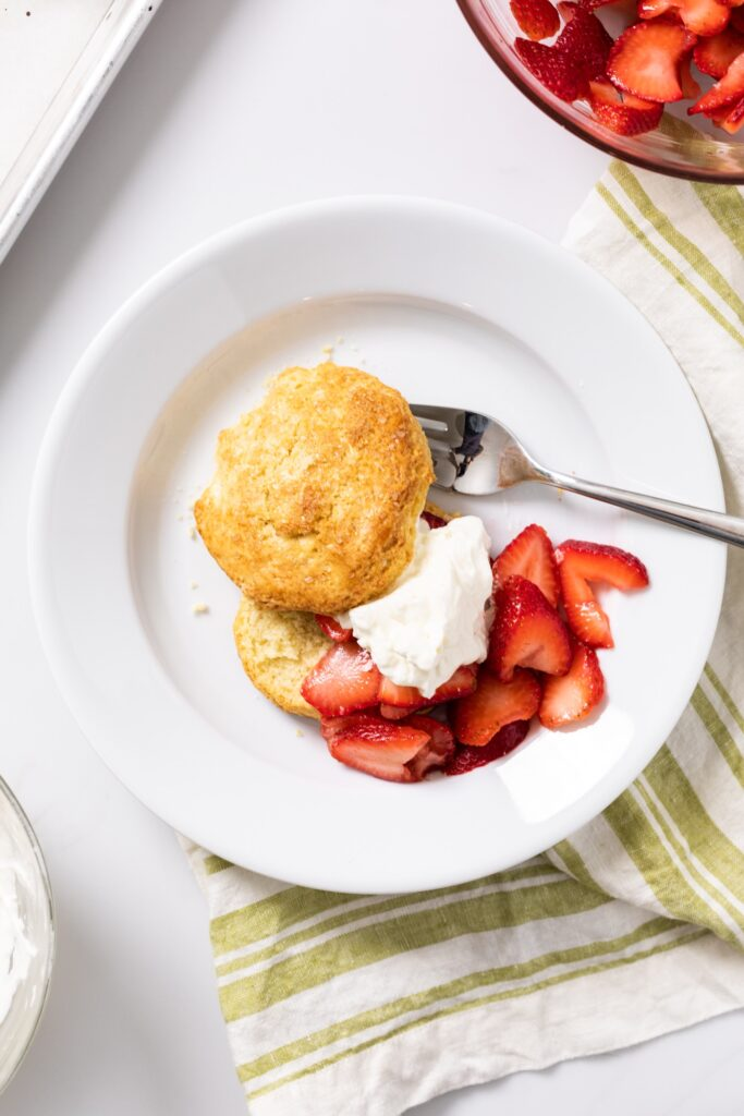 Top down view of white plate filled with strawberry shortcake and biscuit and topped with whipped cream with green napkin underneath