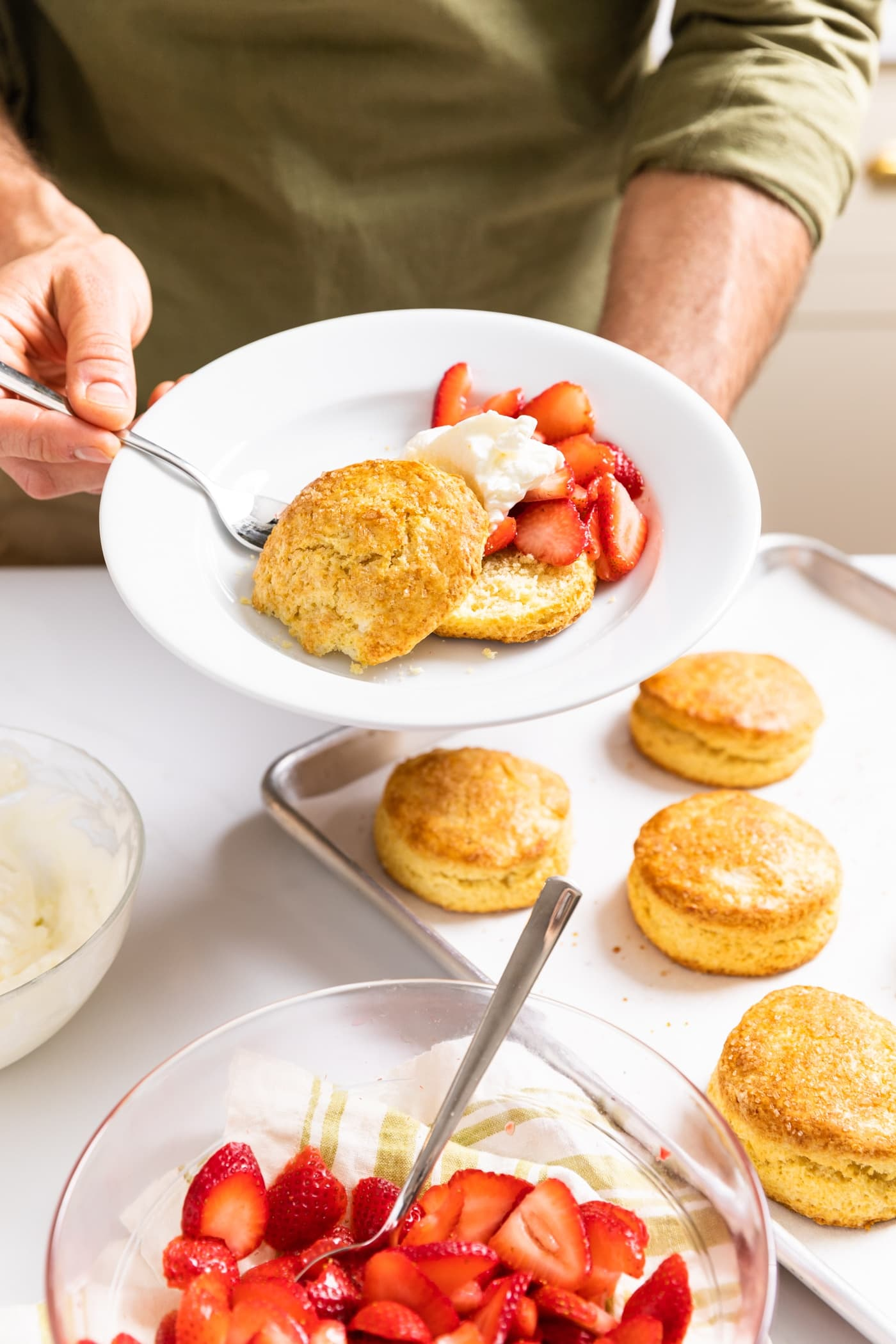 Two hands holding a white plate with yellow biscuit and strawberries topped with whipped cream with rest of components sitting around on countertop