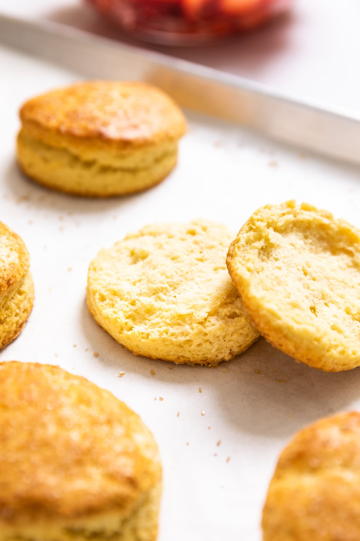Sliced biscuit with both halves sitting close to each on baking dish with other unsliced biscuits around