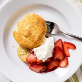 Top down view of white plate with biscuit, strawberries, and whipped cream with striped green napkin underneath