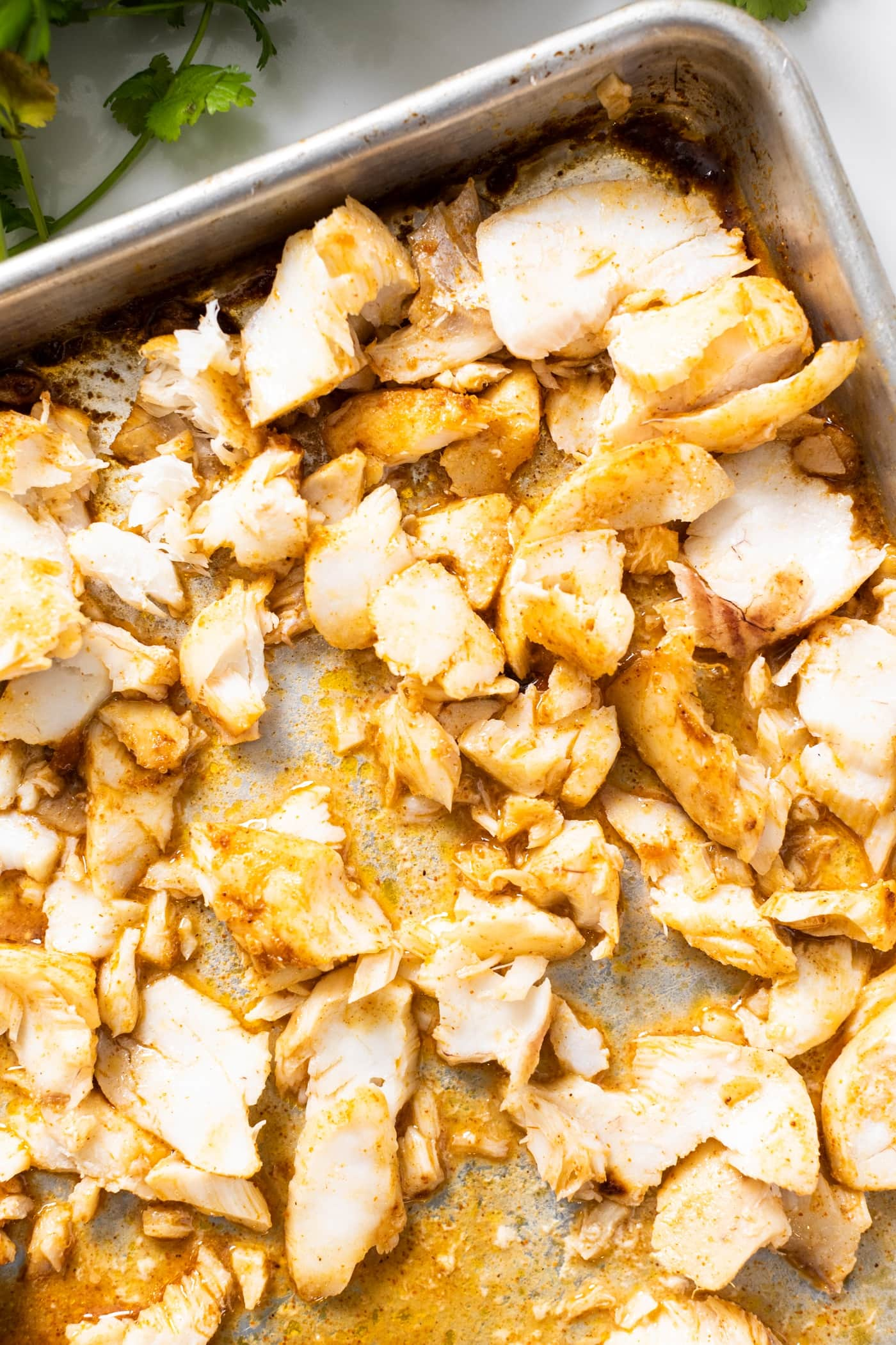 Top down view of shredded cod after being roasted in oven and topped with spices