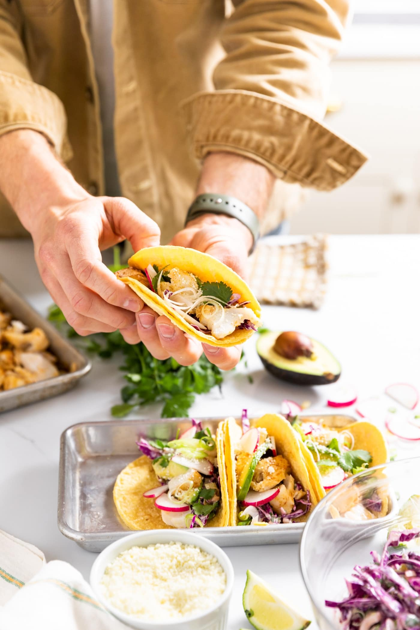 Two hands holding a yellow colored tortilla filled with cod with extra tacos sitting on countertop with toppings all around