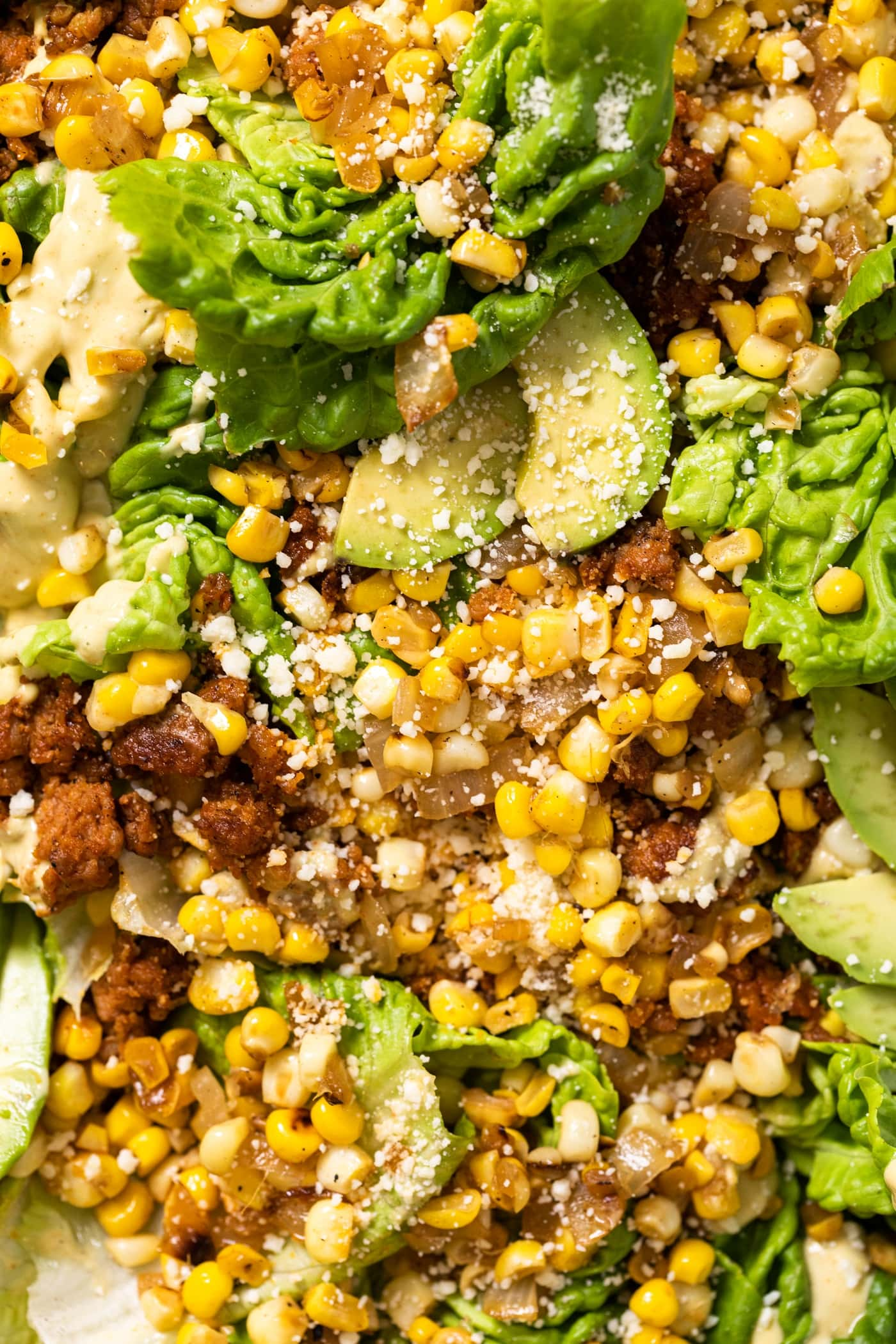 Top down close up view of big pieces of green lettuce topped with sweet corn and chorizo pieces after being cooked and topped with creamy taupe colored dressing