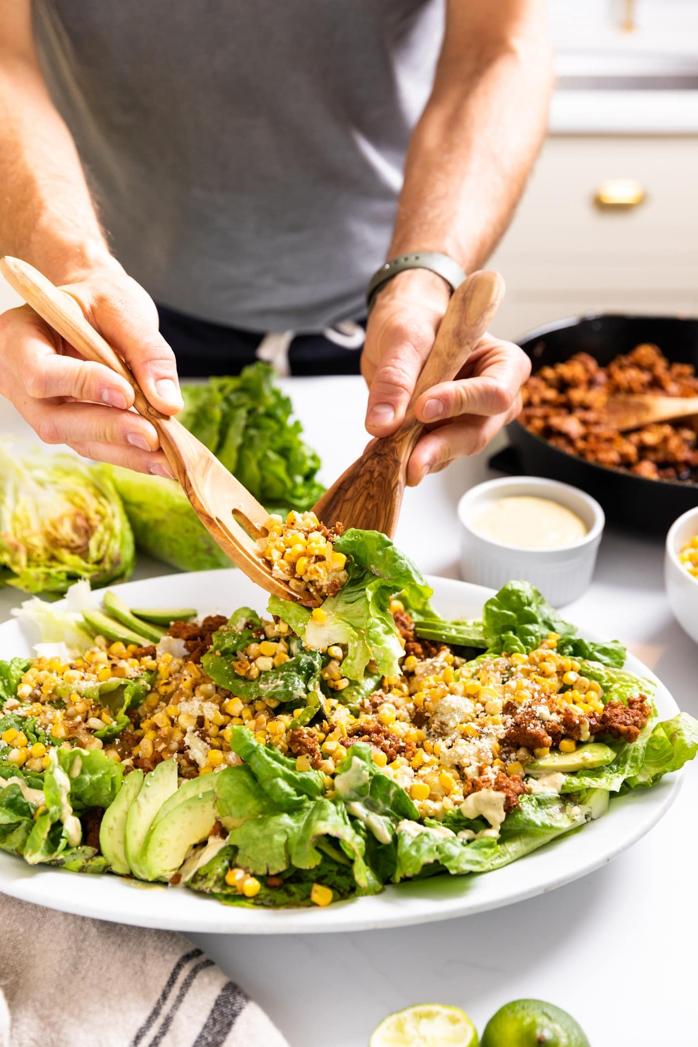 Two hands holding serving tongs full of salad packed with sweet corn and chorizo and lettuce with extra toppings in background