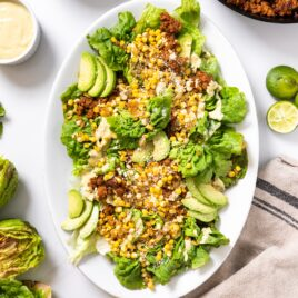 Top down view of white platter sitting on white countertop filled with lettuce and topped with corn and chorizo with extra toppings sitting all around