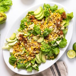 Top down view of white platter sitting on white countertop filled with pieces of lettuce and topped with avocado and sweet corn and chorizo with extra toppings all around