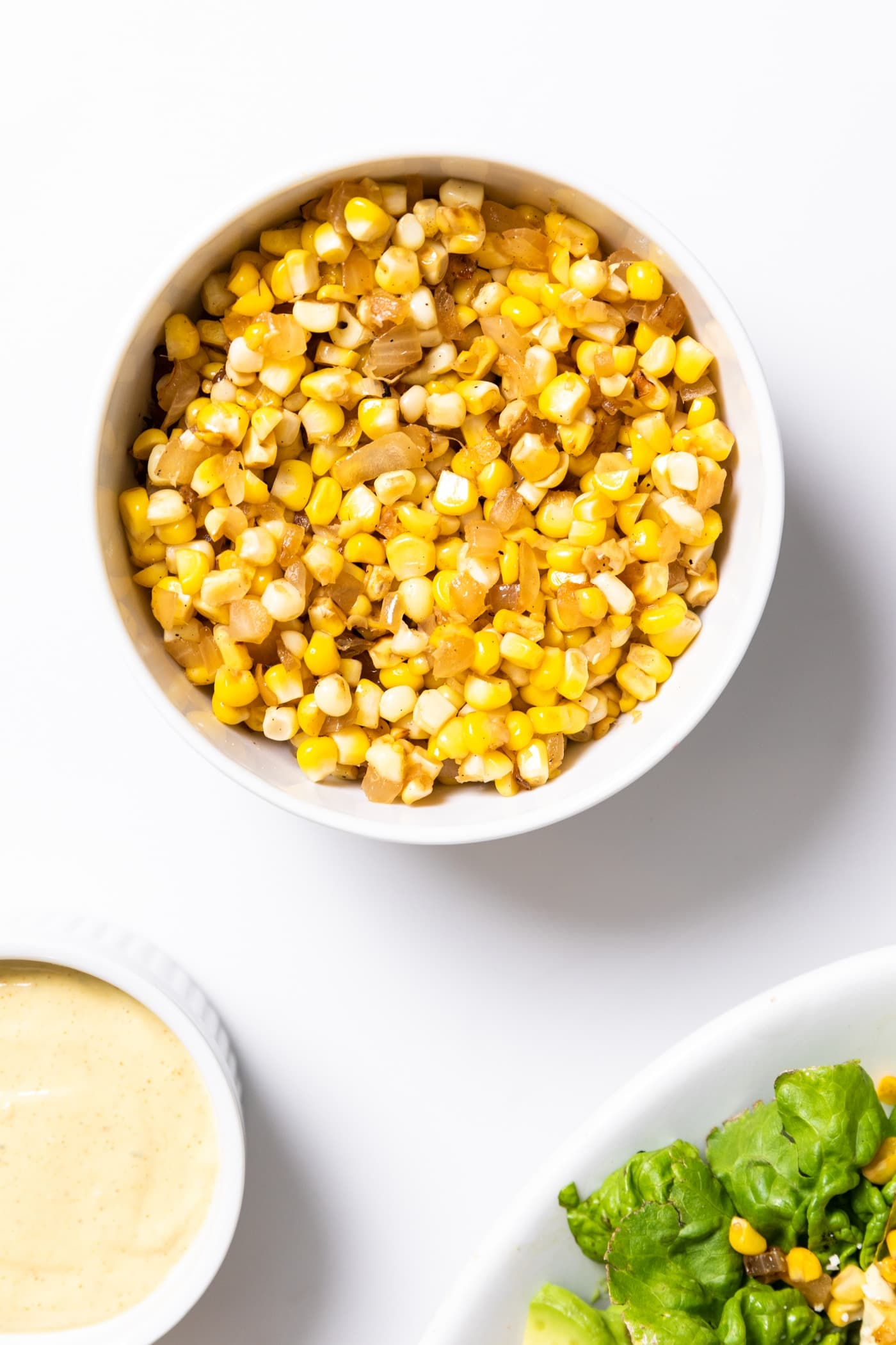 Top down view of cooked combination of sweet corn and onion sitting in white bowl after being on the stove