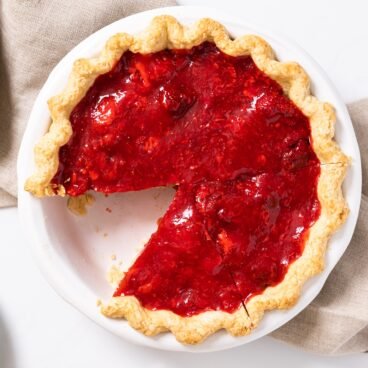 Top down view of red colored strawberry pie with slice cut out sitting on white countertop with taupe colored towel underneath